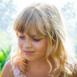 Slightly smiling little blond beautiful Russian girl — Stock Photo
