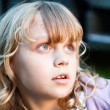 Stock Photo: Closeup portrait of little blond girl looking up with amazement