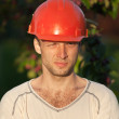 Closeup portrait of young construction worker with squinting eye — Stock Photo