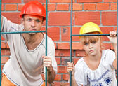 Portrait of young man and his little daughter as a construction — Stock Photo