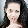 Sensual young woman with her finger on her lips — Stock Photo