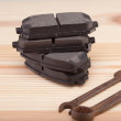 Stock Photo: Brake pads on woden workbench with tools