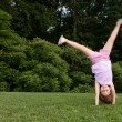 Little girl doing cartwheel — Stock Photo #11454454