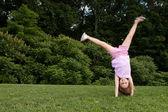 Little girl doing a cartwheel — Stock Photo