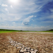 Dramatic sky over dry cracked earth — Stock Photo