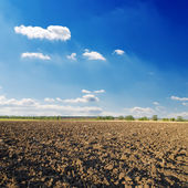 Black ploughed field under deep blue sky with clouds — Stock Photo