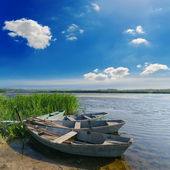 Beautiful river and old boats near green grass under cloudy sky — Stock Photo