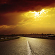 Asphalt road to dramatic sunset - Stock Photo