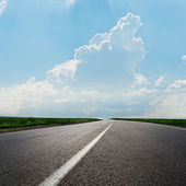 Asphalt road to horizon under cloudy sky — Stockfoto