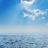 Azzurro del mare e del cielo nuvoloso con sole sopra esso — Foto Stock