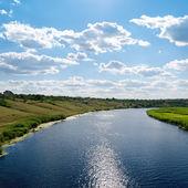 Met het oog op de rivier met reflecties en blauwe bewolkte hemel — Stockfoto
