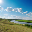 Cloudy sky with sun over river — Stock Photo