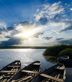 Sunset over river with boats — Stock Photo