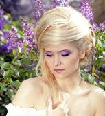 Wellness. porträtt av kvinna modell med blont hår sfär stil över violetta blommor — Stockfoto