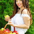 Portrait of happy smiling woman with green apple and basket — Stock Photo #10922574
