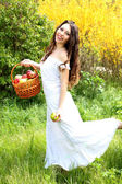 Portrait of happy smiling woman with basket running across field — Стоковое фото