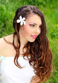 Young woman outdoors portrait. Beautiful face and long curly hea — Stok fotoğraf