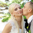 Kissing wedding couple in spring - Stock Photo