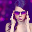 Portrait of fashion young woman in sunglasses isolated on black - Stok fotoğraf