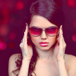 Portrait of fashion young woman in sunglasses isolated on black - Stock Photo