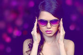Portrait of fashion young woman in sunglasses isolated on black — Stock Photo