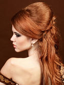 Beautiful woman with red hairstyle luxuriant long hair. — Stock Photo