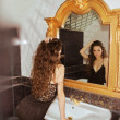 Woman looking at mirror with luxury frame — Stock Photo