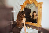 Woman looking at mirror with luxury frame — 图库照片