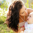 Stock Photo: Mother kissing her dear baby, outdoors portrait