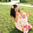 Smiling mother and baby playing in park - Foto de Stock