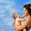 Beautiful Mother with baby over blue sky — Stock Photo