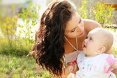 Mother kissing her dear baby, outdoors portrait — Stock Photo