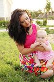 Sonriendo la madre y el bebé jugando en hierba verde — Foto de Stock