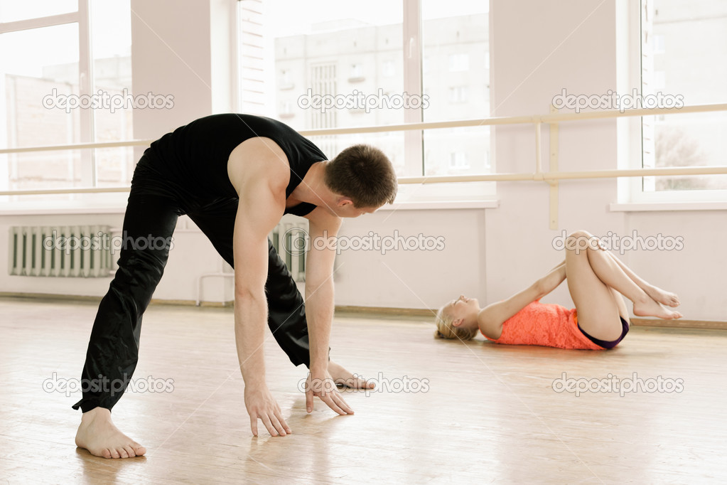 Heterosexual couple in sportswear stretching in aerobics room  Stock Photo #11030428
