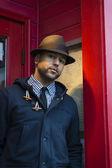 Молодой черный человек стоял в красный дверной проем с коричневый Fredora — Стоковое фото