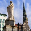 Stockfoto: Sculpture of mwith sword and church behind it