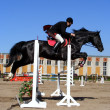 Stock Photo: Mshow jumping on black horse