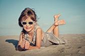Adorable little girl on a sandy beach — Stock Photo