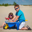 Adorable little girl and boy playing on the sandy beach — ストック写真