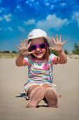 Adorable little girl on a sandy beach — Stock Photo