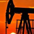 An oil pump jack is silhouetted by the setting sun — Stock Photo #11650282