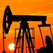 An oil pump jack is silhouetted by the setting sun — Stock Photo #11650307