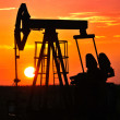 An oil pump jack is silhouetted by the setting sun — Stock Photo #11650346