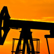 An oil pump jack is silhouetted by the setting sun — Stock Photo #11650406
