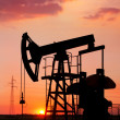 An oil pump jack is silhouetted by the setting sun - Foto de Stock