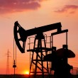 An oil pump jack is silhouetted by the setting sun — Stock Photo #11650460
