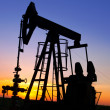 An oil pump jack is silhouetted by the setting sun — Stock Photo #11650529