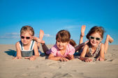 Adorable three little girl playing on the sandy beach — Stock Photo