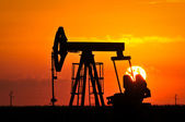 Un conector de la bomba de aceite se recorta por la puesta de sol — Foto de Stock