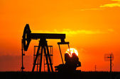 An oil pump jack is silhouetted by the setting sun — Foto Stock